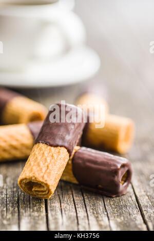 Dessert sucré. rouleaux de biscuits au chocolat avec glaçage sur vieille table en bois. Banque D'Images