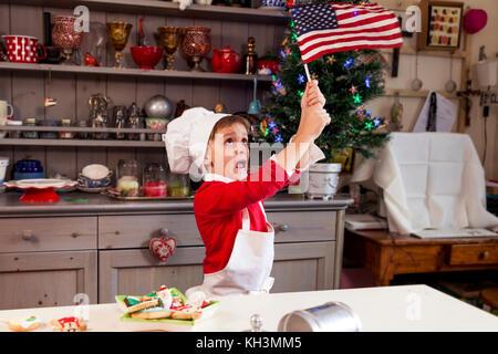 Jeune homme brandissant le drapeau américain dans la cuisine pour Noël Banque D'Images