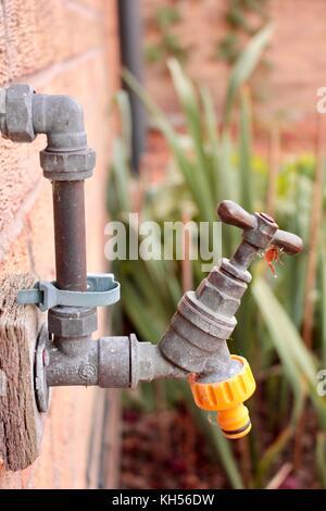 Robinet d'eau extérieur sur mur cuisine avec connecteur flexible jaune attachés. Banque D'Images