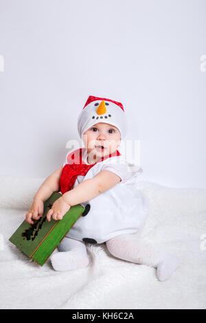 c273a58627cd6 Bébé fille attrayante étonné en costume de Noël assis et d avoir du plaisir  Banque