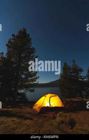 Une tente est allumé en dessous du ciel étoilé sur la rive d'un lac tout en camping dans l'oregon. Banque D'Images
