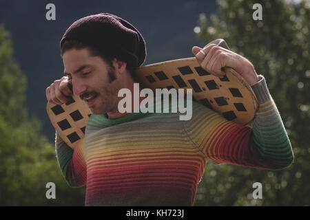 Thoughtful man holding skateboard dans skate park Banque D'Images