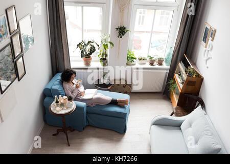 Belle femme tenant une tasse de café à la maison