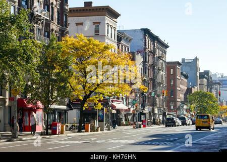 New york city - circa 2017: la lumière du soleil brille sur les arbres aux couleurs automnales avec un taxi roulant Banque D'Images
