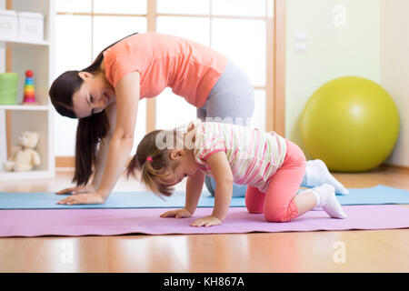 Mère et enfant fille pratiquant le yoga ensemble à la maison. sport et famille concept Banque D'Images
