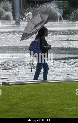 Femme marche dans la pluie et le vent, avec brolly intérieur à l'extérieur, en passant par la piscine miroir et Banque D'Images