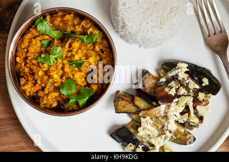 Repas indien avec le masoor dal - curry de lentilles, dahi baingan, riz et salade Banque D'Images