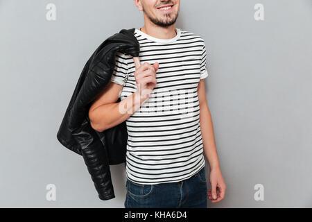 Portrait of smiling man holding sa veste sur l'épaule sur fond gris Banque D'Images
