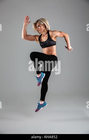 Portrait d'une femme adulte musculaire remise en forme de saut arrière-plan gris Banque D'Images