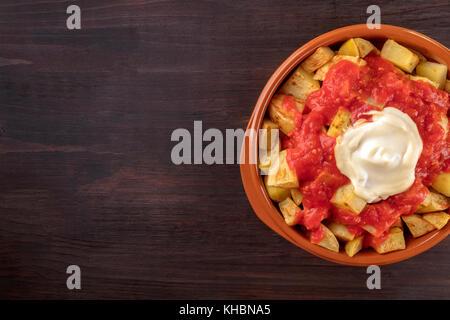 Un passage libre d'un bol de patatas bravas, espagnol traditionnel plat de frites avec deux sauces, sur une texture Banque D'Images
