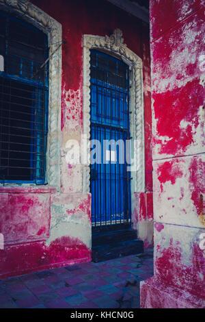 Mur peint peeling rouge et bleu porte pour une propriété sur le Malecon de La Havane, Cuba Banque D'Images