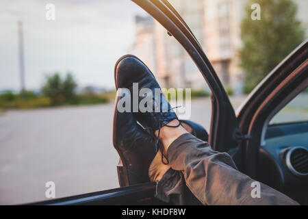 L'homme de dormir dans sa voiture, l'étirement des jambes du pilote fatigué Banque D'Images