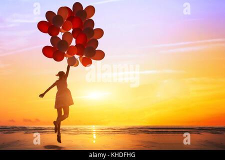Bonheur ou dream concept, silhouette de femme heureuse sautant avec ballons multicolores au coucher du soleil sur Banque D'Images