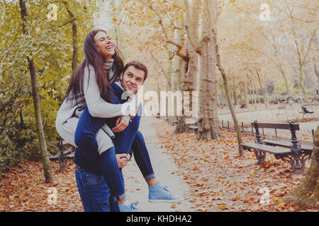Man carrying woman piggyback, dating, young couple laughing in autumn park Banque D'Images