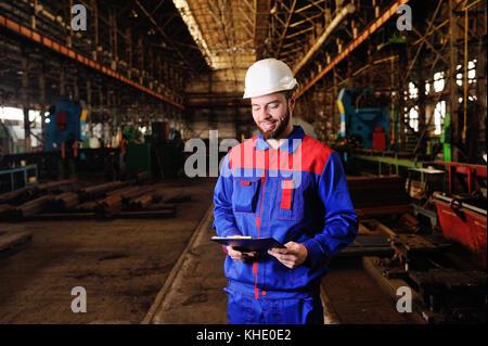 Travailleur dans un casque avec une tablette Banque D'Images
