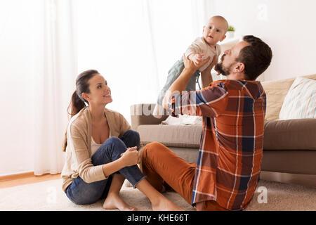 Heureux père et mère jouer avec bébé à la maison Banque D'Images