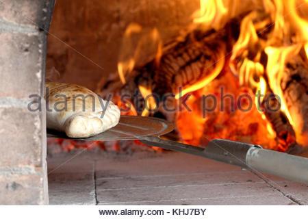 Pizza calzone extraire hors de tho four à bois par shovel Banque D'Images