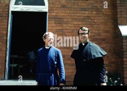 Une photographie de deux prêtres à l'extérieur d'une église, le prêtre sur la gauche porte une robe bleue et celle Banque D'Images
