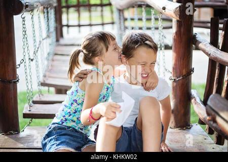 Deux jeunes enfants de race blanche en éclatant de rire. Soeur essaie d'embrasser son frère sur une joue. Banque D'Images