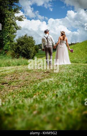 Photo d'un jeune couple marchant dans un chemin à travers un parc se tenant la main. Banque D'Images