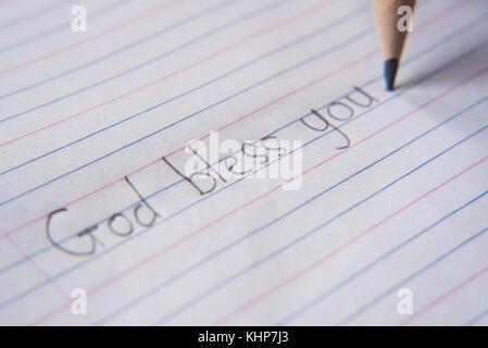 """À l'aide de l'écriture sur un papier-crayon.écrire: """"Dieu vous bénisse"""" Banque D'Images"""