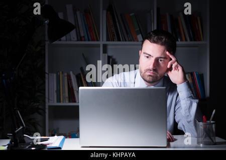 Businessman working et regarder à l'écran de l'ordinateur portable nuit Banque D'Images