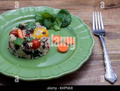 Plaque verte avec Salade de quinoa en forme de petit gâteau sur une table en bois, - le quinoa est une pseudo-grain qui a tous les neuf acides aminés essentiels et acides