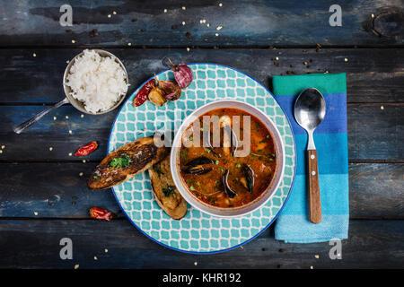 Fruits de mer soupe de tomate avec du pain et du riz pour la garniture sur un fond de bois de couleur. vue d'en Banque D'Images