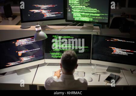 Méconnaissable développeur de logiciels aux cheveux gris et l'écriture de code alors qu'il était assis en face de Banque D'Images