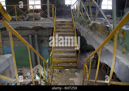 Escalier avec balustrade jaune dans un intérieur industriel ruiné. oublié ancienne usine.