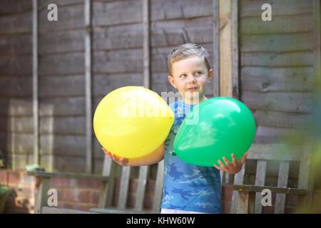 Jeune garçon en jardin, holding balloons Banque D'Images