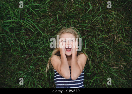 Passage portrait of girl lying on grass avec les mains sur ses joues Banque D'Images