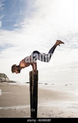 Jeune homme, formation doing handstand avec jambes sur la plage en bois posts Banque D'Images
