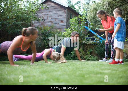 Dans l'exercice de la famille jardin, faisant push-ups Banque D'Images