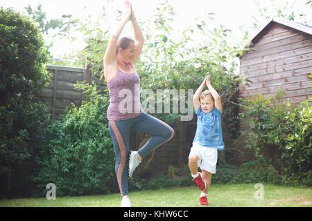 La mère et le fils dans l'exercice de jardin, debout dans la position de yoga Banque D'Images