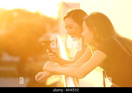 Deux amis heureux en utilisant un téléphone intelligent dans une chambre balcon au coucher du soleil avec une lumière Banque D'Images