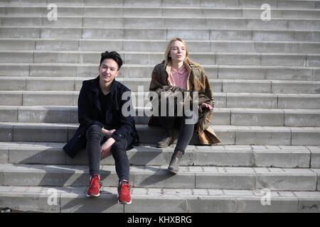 Un couple d'amis sont assis sur les marches Banque D'Images