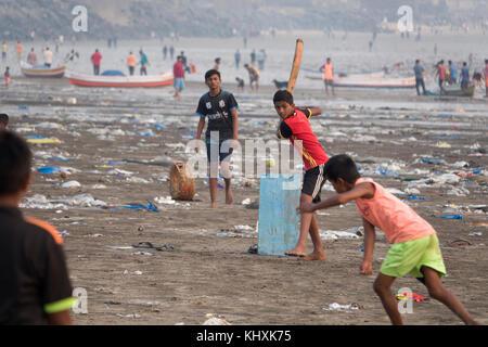 Enfants jouant cricket parmi les déchets plastiques et autres déchets sur la plage de versova, Mumbai, Inde
