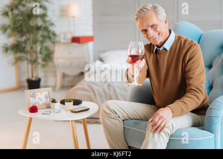 Senior joyeux monsieur avec verre de vin de l'appareil photo en souriant Banque D'Images