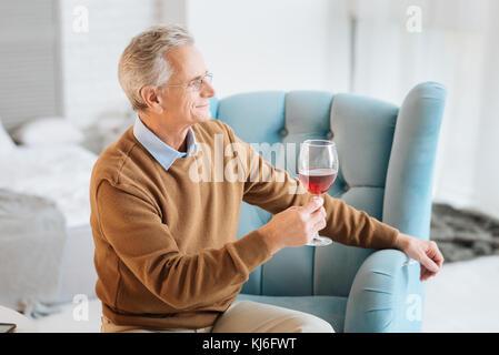 Ambiance vieux monsieur appréciant le vin rouge et souriant Banque D'Images