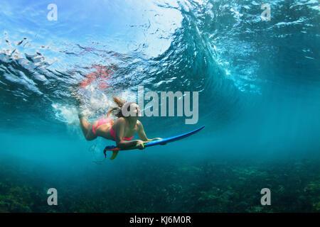 Active girl in bikini en action. femme surfeur surf avec sous-marine Plongée sous casser grande vague de vie d'adolescent.. Banque D'Images
