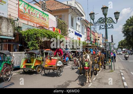 Vélos-pousse / becak et calèches pour les transports publics à Jalan Malioboro, principale rue commerçante à Yogyakarta, Banque D'Images
