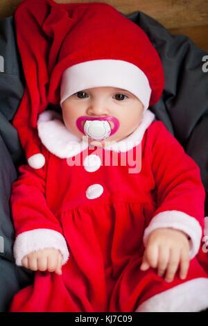 Baby Girl in santa claus hat costume et se dresse au milieu de l'oreiller avec sucette dans sa bouche. libre. Banque D'Images