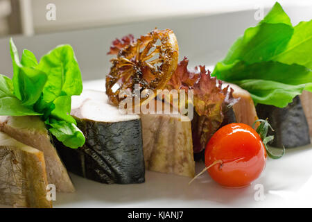 Maquereau fumé à chaud. En tranches avec les herbes et tomates cerises Banque D'Images