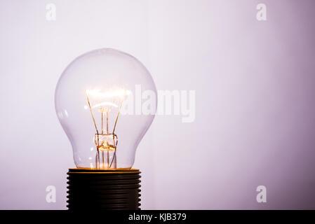 Photo horizontale avec une seule ampoule de verre. l'ampoule est allumée et que le fil à l'intérieur est chaud et Banque D'Images