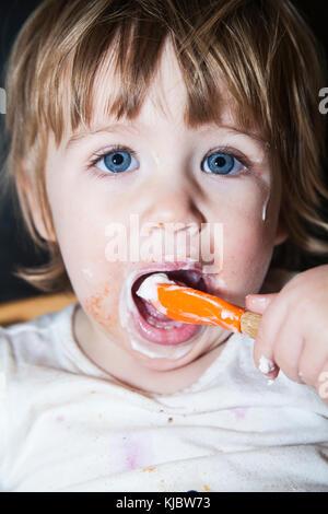 Enfant malpropre de manger avec une cuillère Banque D'Images