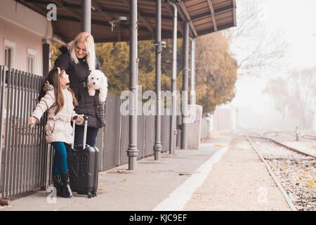 Mère, fille, et leur attente de la gare de train sur la plate-forme. enfant et femme en attente de train et avion d'un voyage, voyage, personnes.