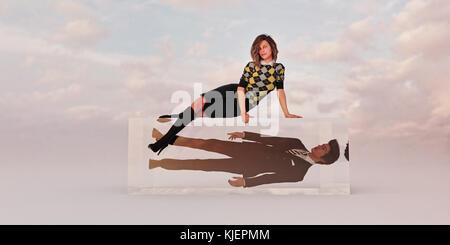 Confident businesswoman sitting on cube avec businessman coincé à l'intérieur Banque D'Images