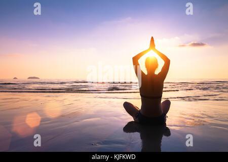 Le yoga et la méditation sur la plage paisible calme au coucher du soleil, fit young woman Banque D'Images