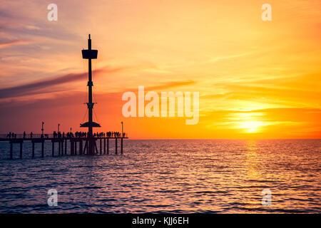 Les personnes bénéficiant de coucher du soleil à partir de la jetée de Brighton, dans le sud de l'Australie
